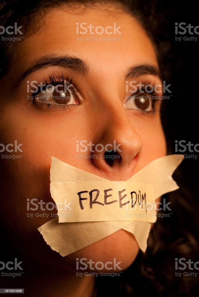 Woman with pieces of tape with the word freedom on her mouth stock photo