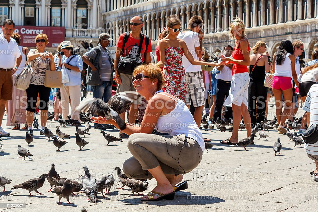 Woman with pigeons on St Mark's Square royalty-free stock photo