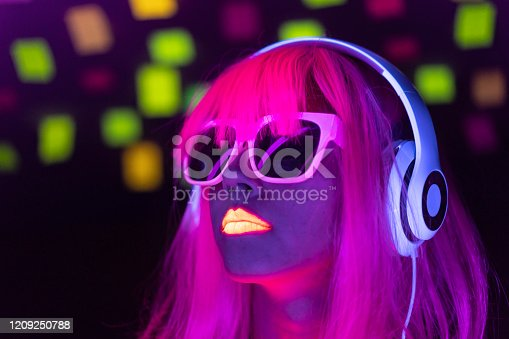 Woman with glowing makeup in black light. Woman with pink colored hair and sunglasses listening music with neon colored headset.