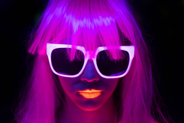 Woman with pink colored hair, neon makeup and sunglasses