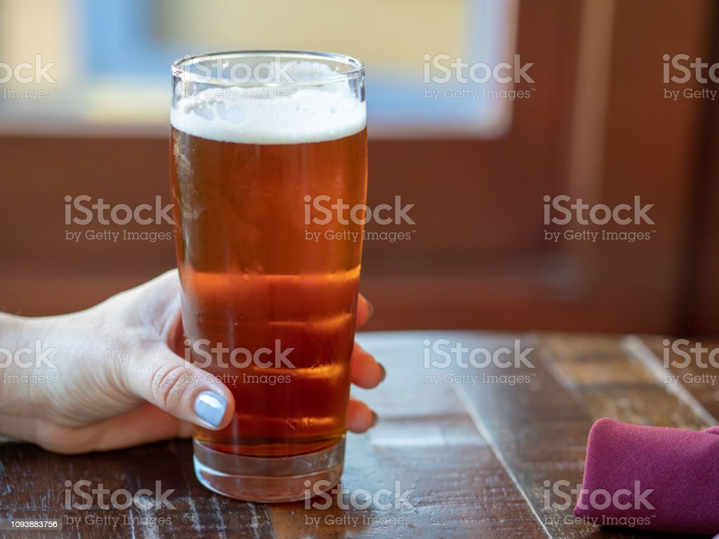 Woman with pink fingernails holding glass of IPA beer on restaurant table – zdjęcie