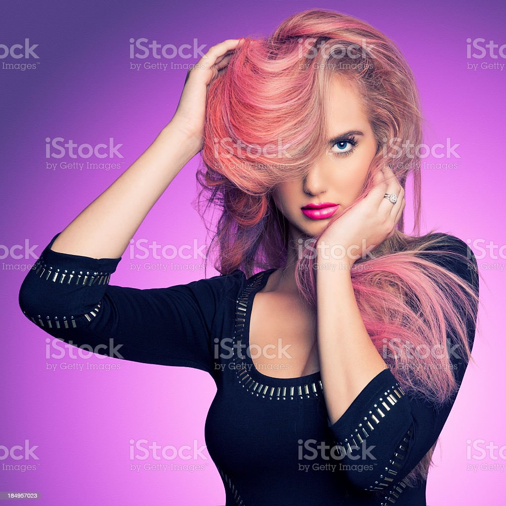 Woman with pink hair over one eye in a black dress royalty-free stock photo