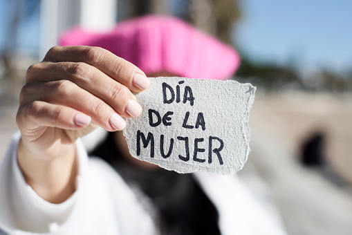 woman with pink hat and text womens day in spanish