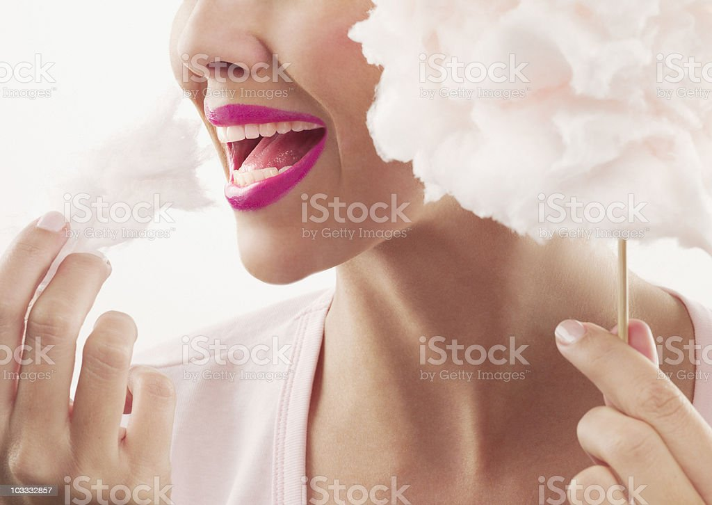 Woman with pink lipstick eating cotton candy stock photo