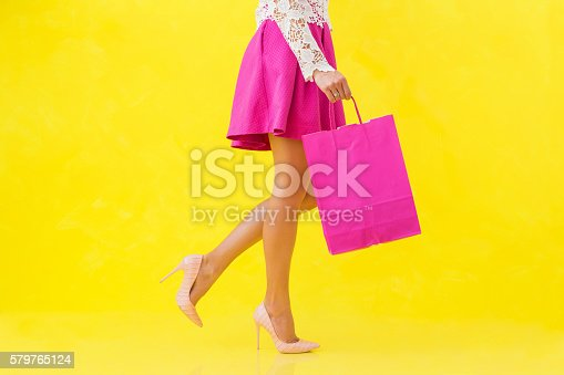 istock Woman with pink shopping bag 579765124