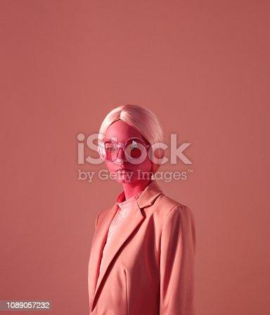 Woman with pink skin make-up, pink eyeglasses and pink blazer