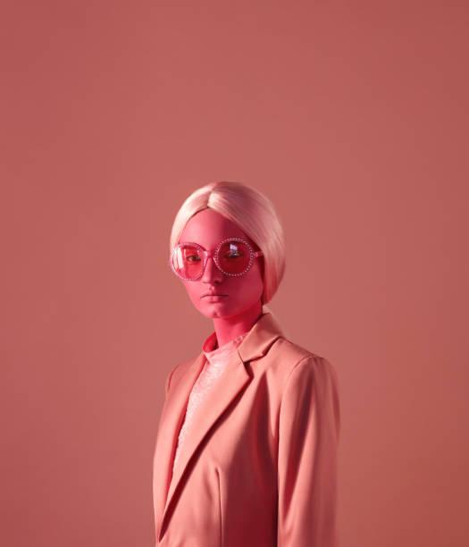 femme avec la peau rose et lunettes roses - fond couleur uni photos et images de collection