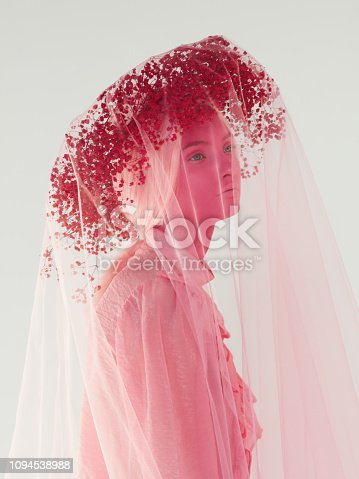 Woman with pink skin make-up, pink wreath, veil and top