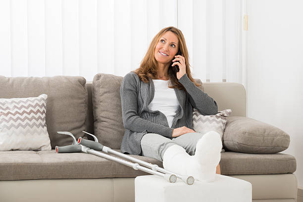 woman with plastered leg talking on mobile phone - broken leg stock photos and pictures