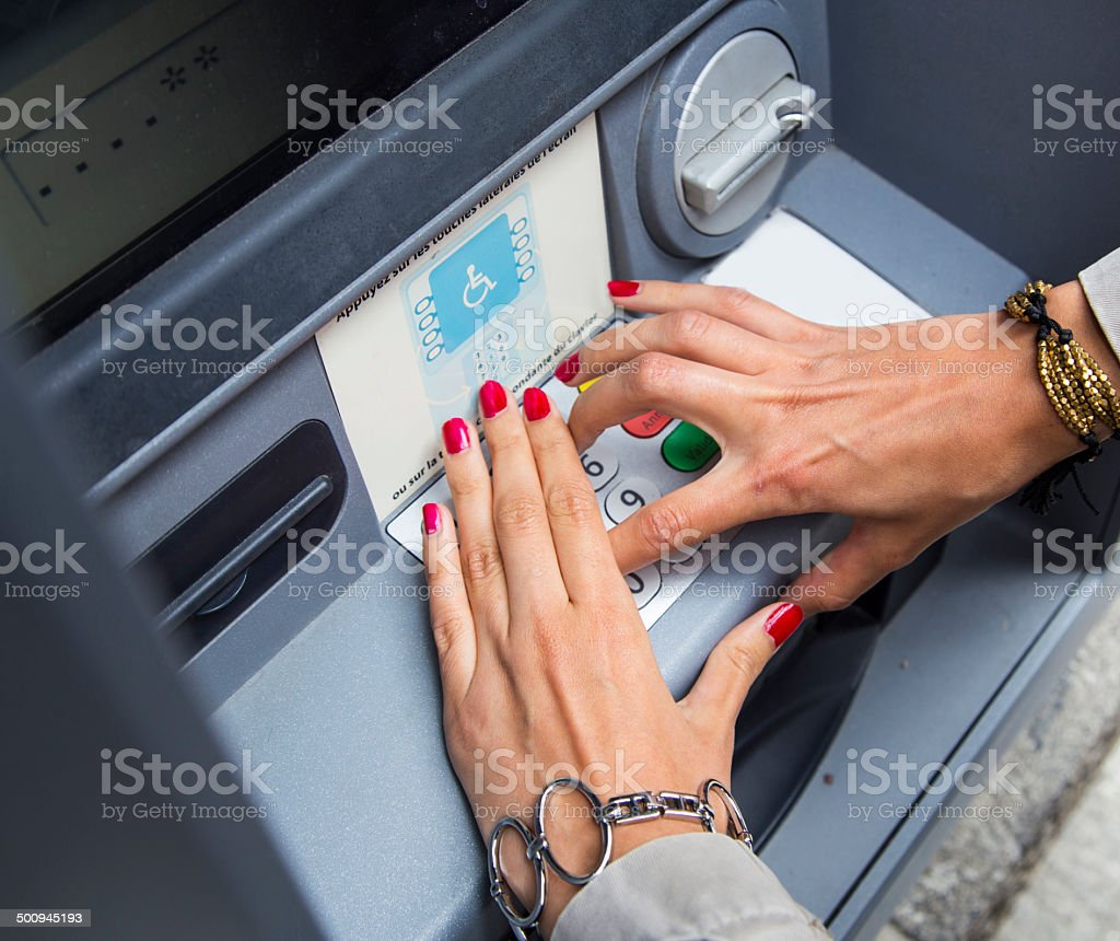 woman with polished nails withdrawing money at atm stock photo