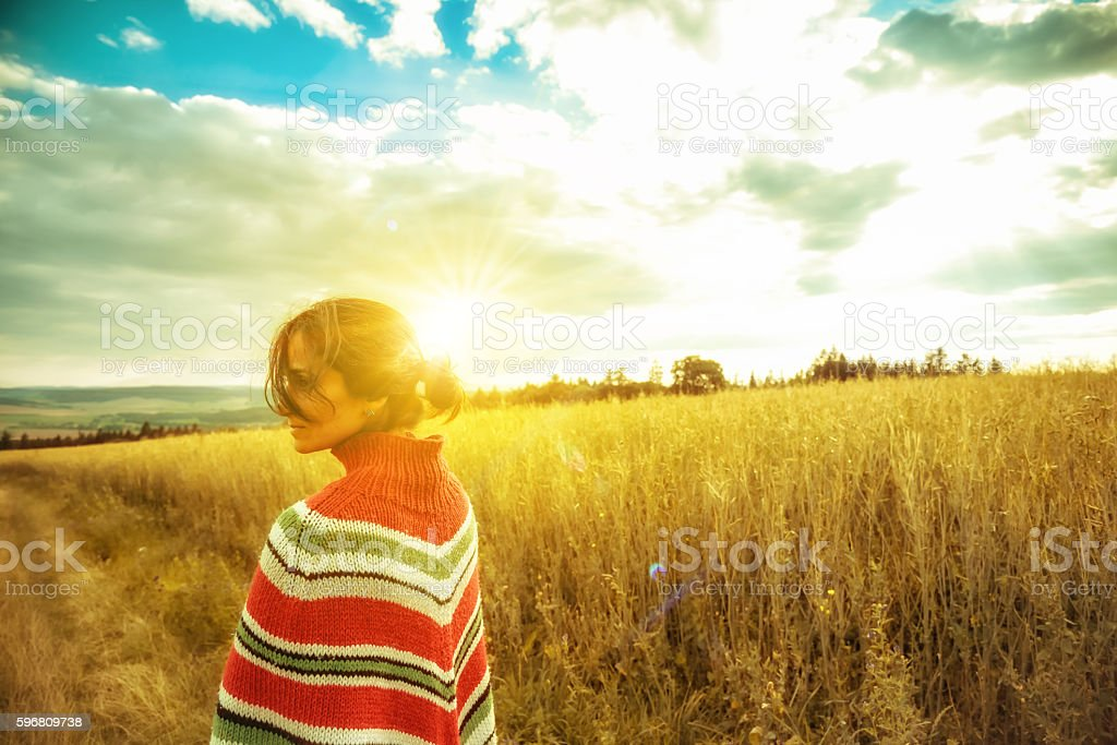woman with poncho in summer landscape at sunset hour stock photo