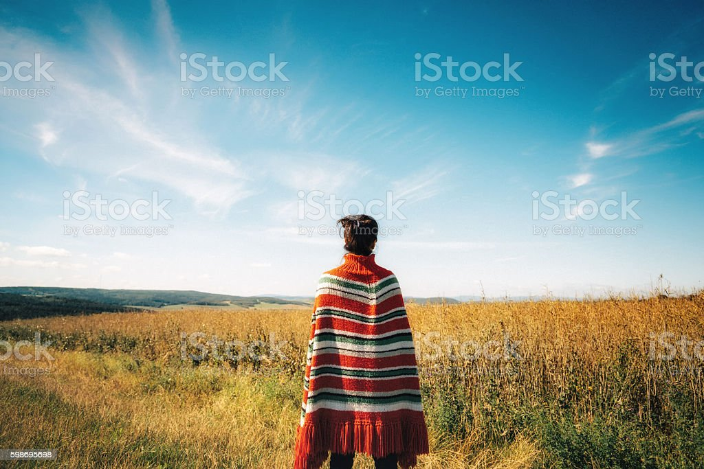 woman with poncho looking over late summer landscape stock photo