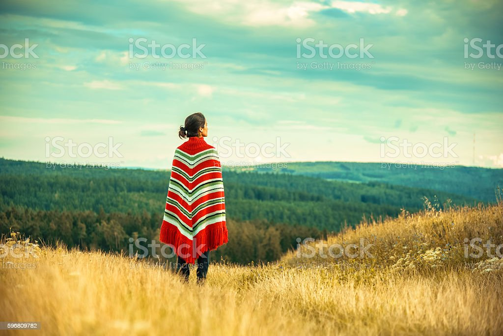 woman with poncho looking over the landscape stock photo