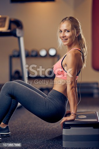 Smiling Caucasian blonde woman with ponytail in sportswear doing exercises on steps while looking at camera. Gym interior, healthy lifestyle concept.