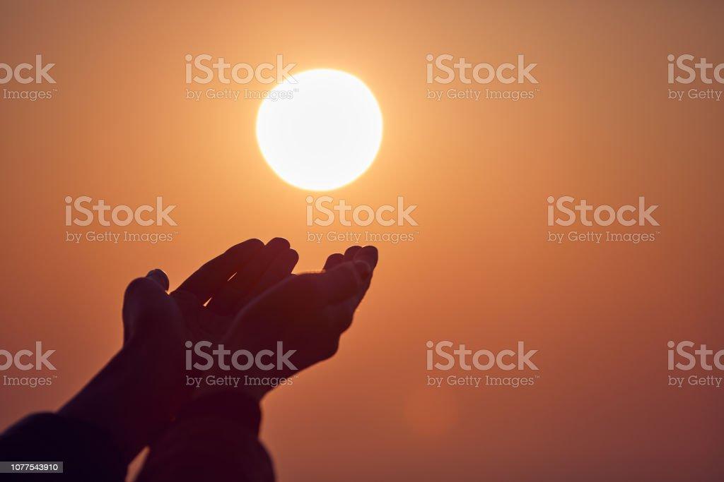 Woman with praying arms enjoying the sunrise / sunset time. stock photo
