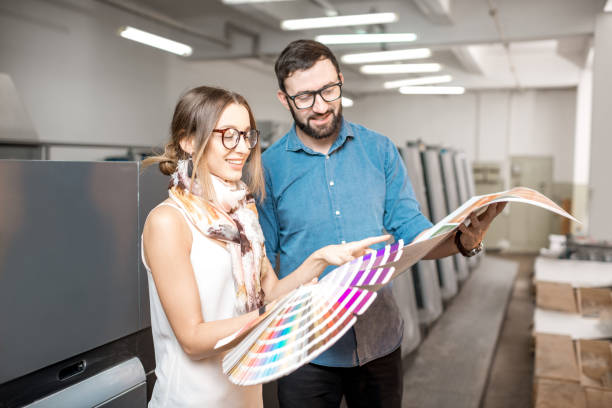 Woman with print operator at the manufacturing Young woman designer and print operator working together with color swatches standing at the print manufacturing printing plant stock pictures, royalty-free photos & images