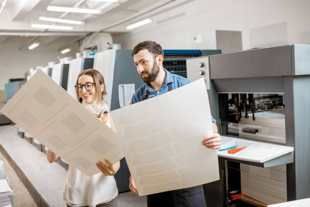 Woman with print operator at the printing manufacturing Young woman designer and print operator working with paper print at the print manufacturing with offset machine on the background printing plant stock pictures, royalty-free photos & images