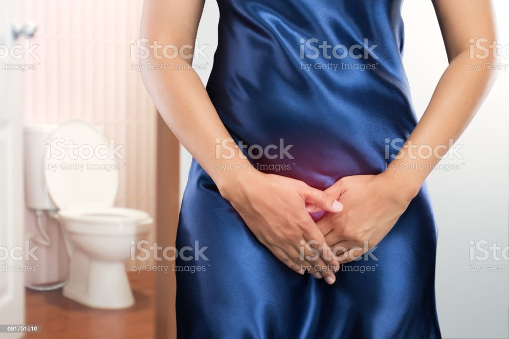 Woman with prostate problem in front of toilet bowl. Lady with hands holding her crotch, People wants to pee - urinary incontinence concept stock photo