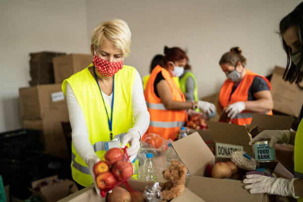 Woman with protective face mask helping collecting food in a homeless shelter stock photo