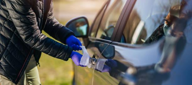 Frau mit Schutzhandschuhen desinfizieren das Auto mit antibakteriellen Feuchttüchern. – Foto