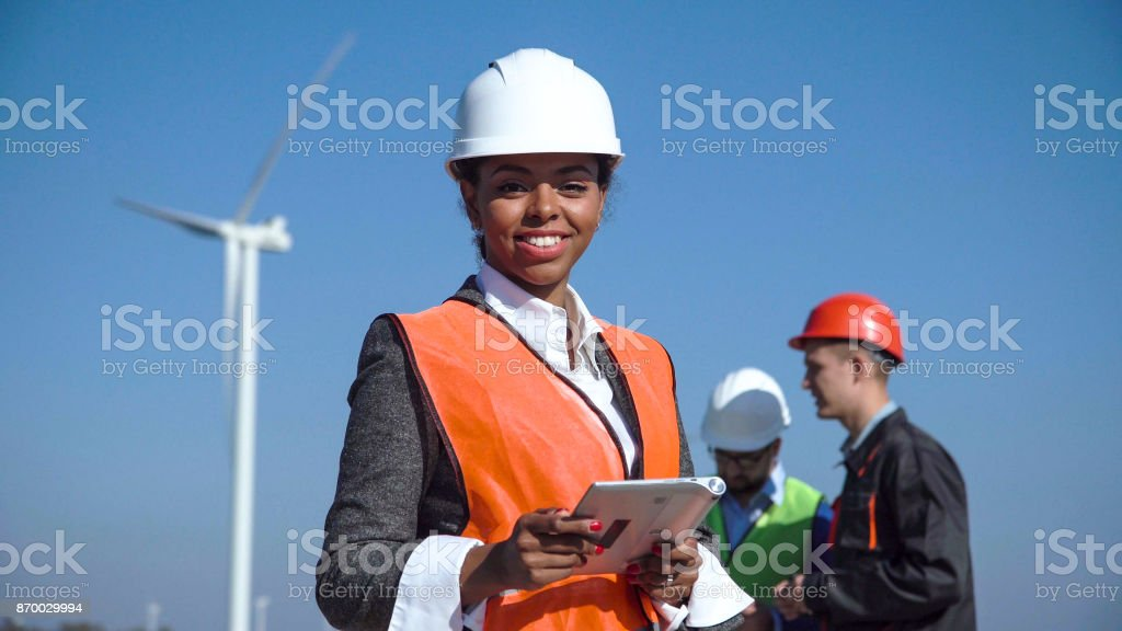 Woman with protective helmet against wind turbine royalty-free stock photo