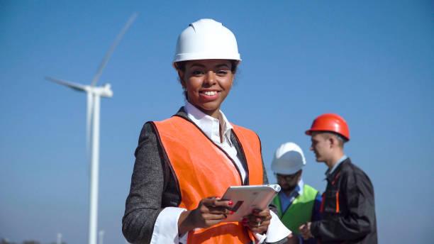 frau mit schutzhelm gegen windturbine - generator text stock-fotos und bilder