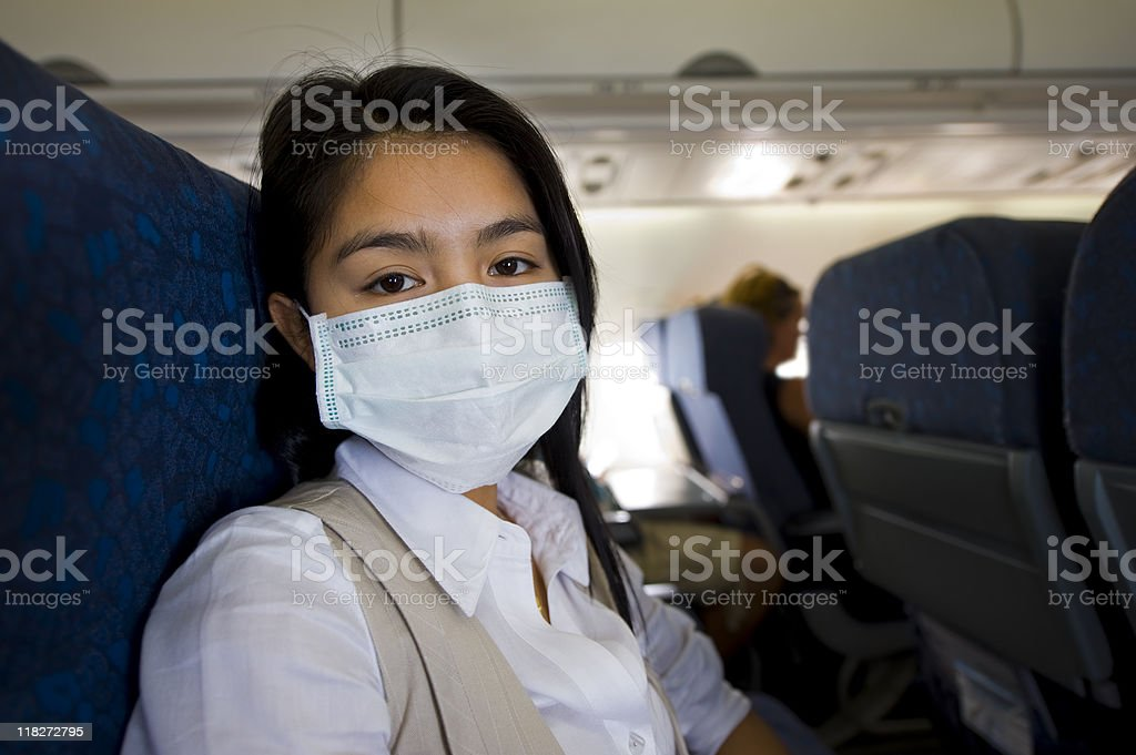 woman with protective mask in a plane stock photo