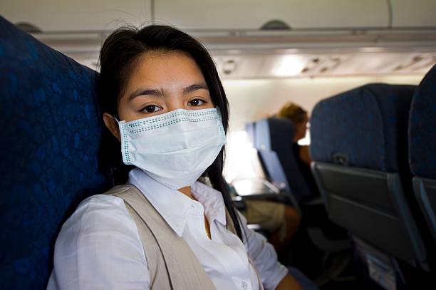 donna con maschera protettiva in un piano - sars foto e immagini stock