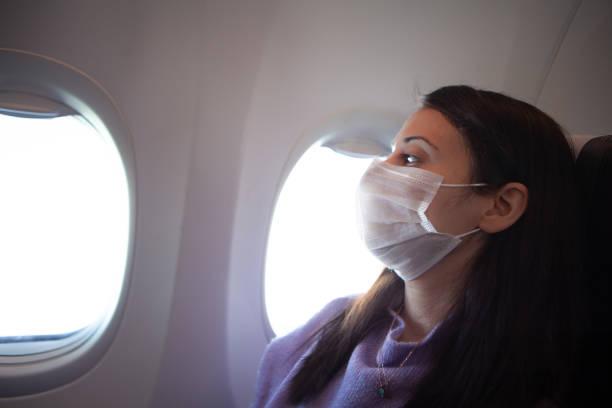 woman with protective mask in a plane stock photo , coronavirus - covid flight imagens e fotografias de stock