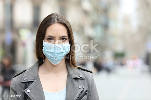 istock Woman with protective mask looking at camera on street 1211384722