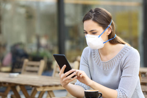 Woman with protective mask looking at phone on a cafe stock photo