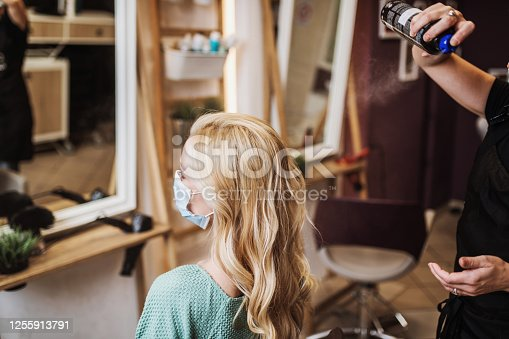 Professional hairdresser making a beautiful hairstyle of young adult woman after dyeing hair and making highlights in hair salon. They wearing face protective masks. Pandemic lifestyle.