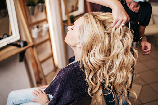 Professional hairdresser making a beautiful hairstyle of young adult woman after dyeing hair and making highlights in hair salon. Modern lifestyle concept.