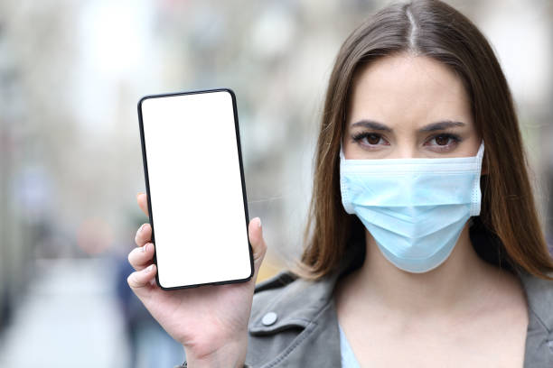 Woman with protective mask showing phone screen stock photo