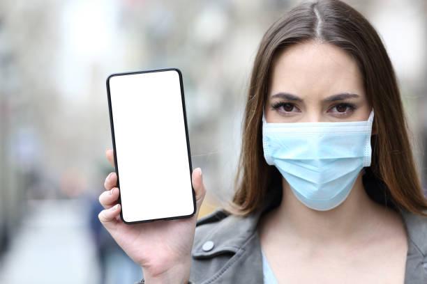 Frau mit Schutzmaske zeigt Handy-Bildschirm – Foto