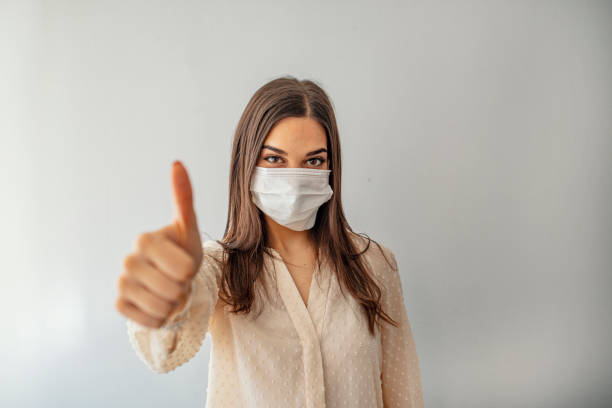 woman with protective mask showing thumb up, and looking at camera - adenovirus foto e immagini stock