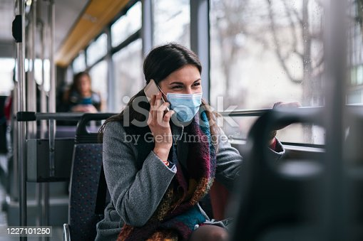 Woman with protective face mask sitting in city transport and talking on the phone.