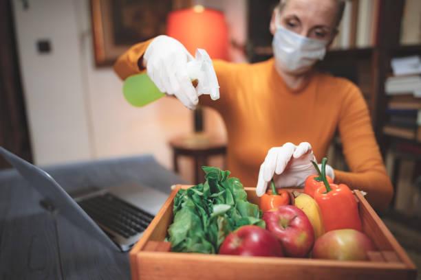Frau mit Schützenmaske Sprühen sterilisierende Chemikalie auf die Lebensmittel aus dem Internet-Lieferung bestellt. – Foto