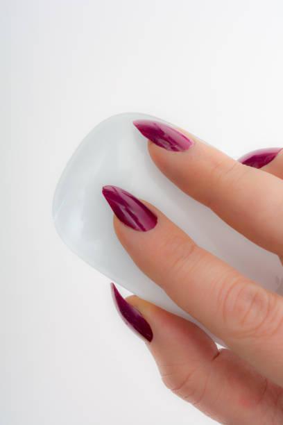 frau mit lila maniküre mit einer weißen maus - nails stiletto stock-fotos und bilder