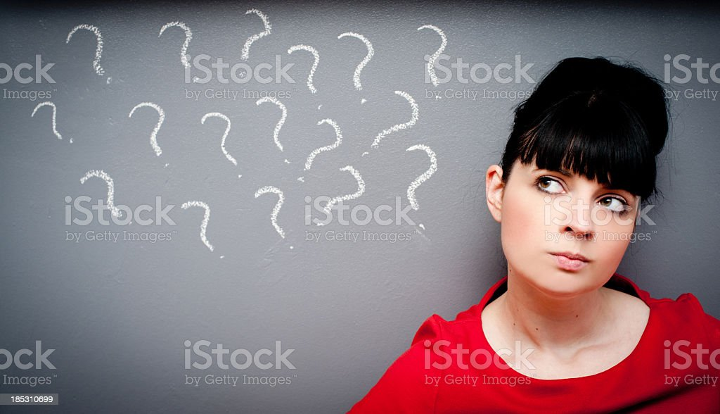 Woman with questioning look on wall with question marks royalty-free stock photo