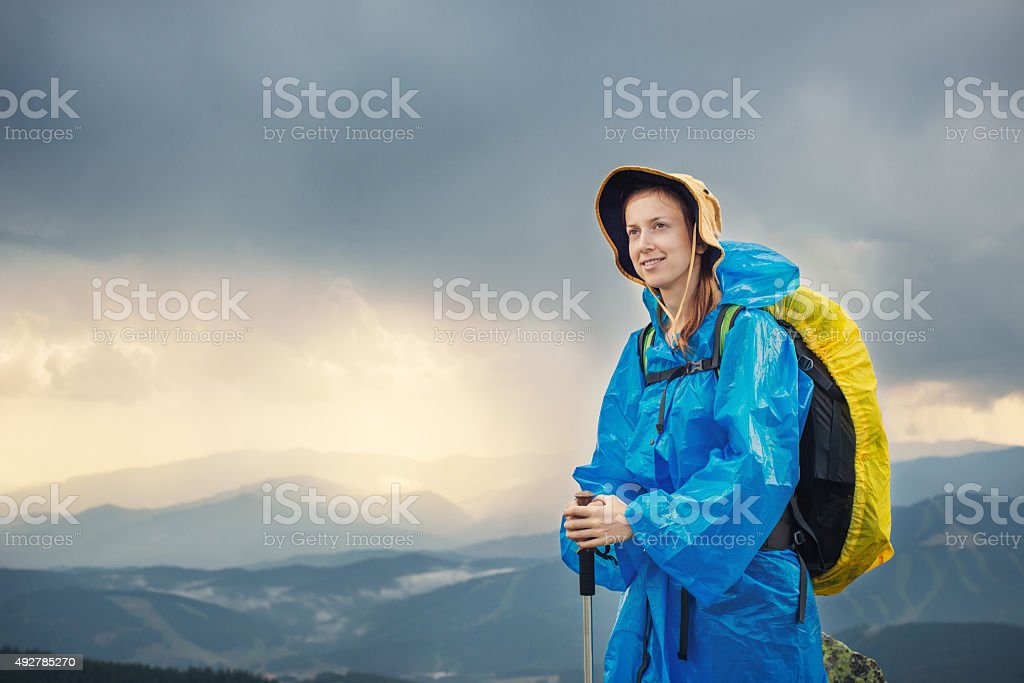 Woman with raincoat hiking in rainy weather stock photo