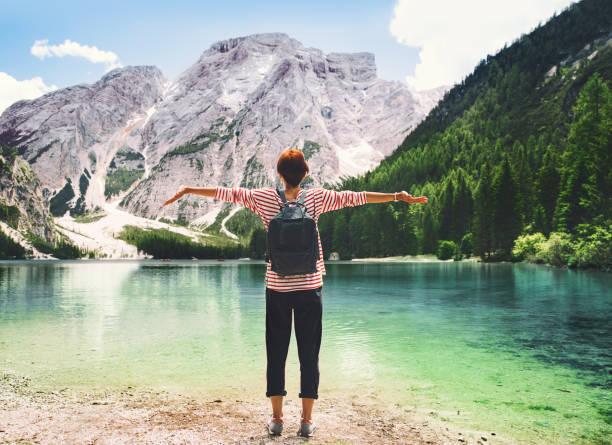 Mujer con los brazos levantados para arriba mirar lago Braies con montañas en el fondo. - foto de stock