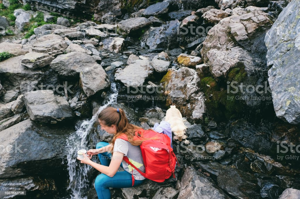 Hiker and her dog drink water from the nature river in Norway