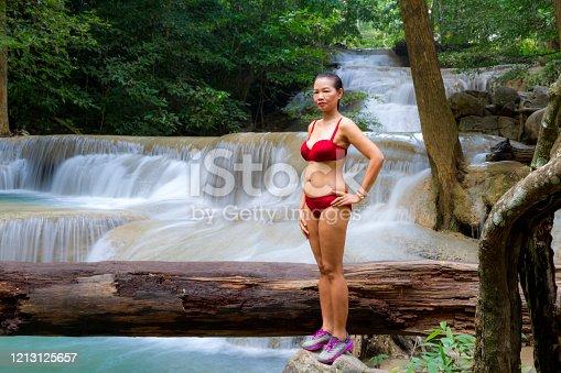 Woman with red bikini enjoy at Erawan Waterfall and natural in Kanchanaburi province Thailand. Erawan Waterfall Is a beautiful and famous water fall.