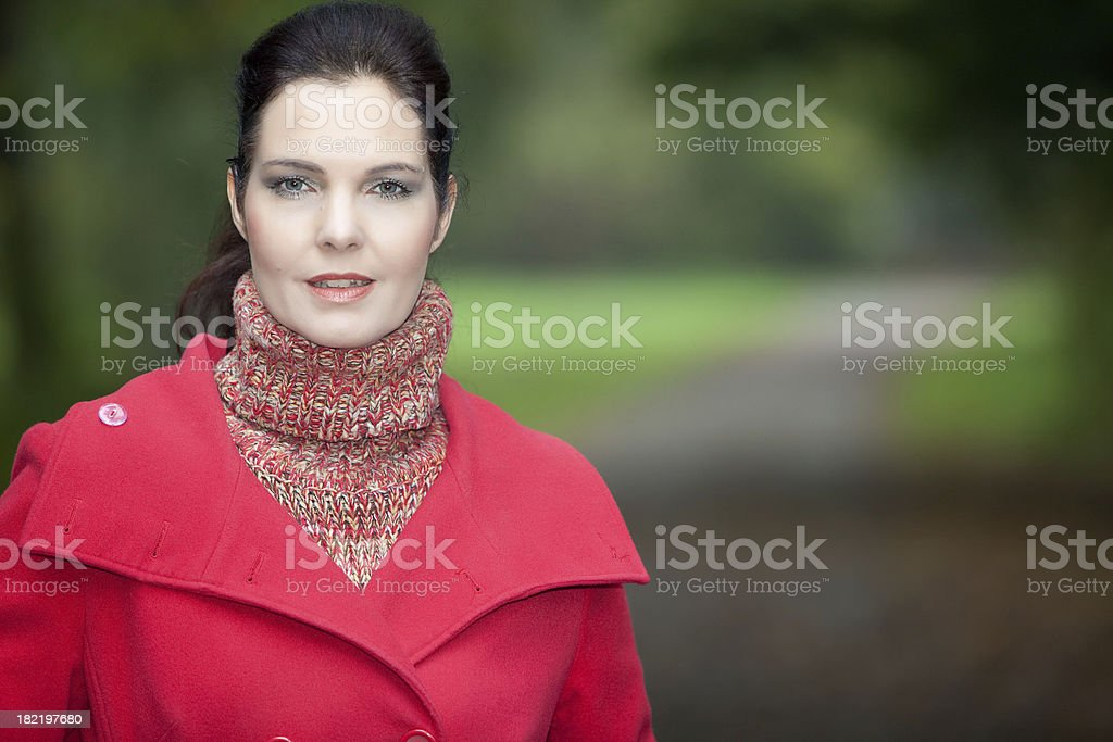 Woman with red coat in the park stock photo