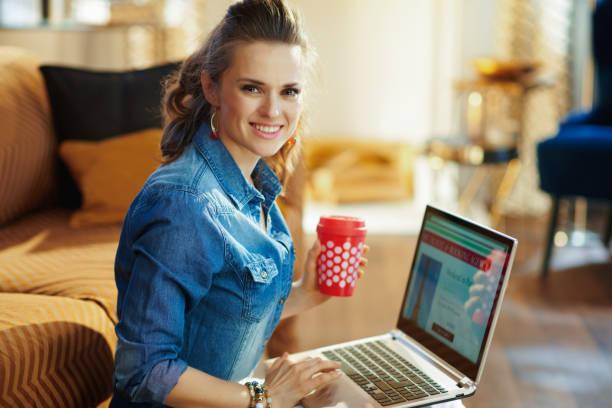 frau mit roter kaffeetasse und online-reise-seite auf dem laptop - billigflüge buchen stock-fotos und bilder