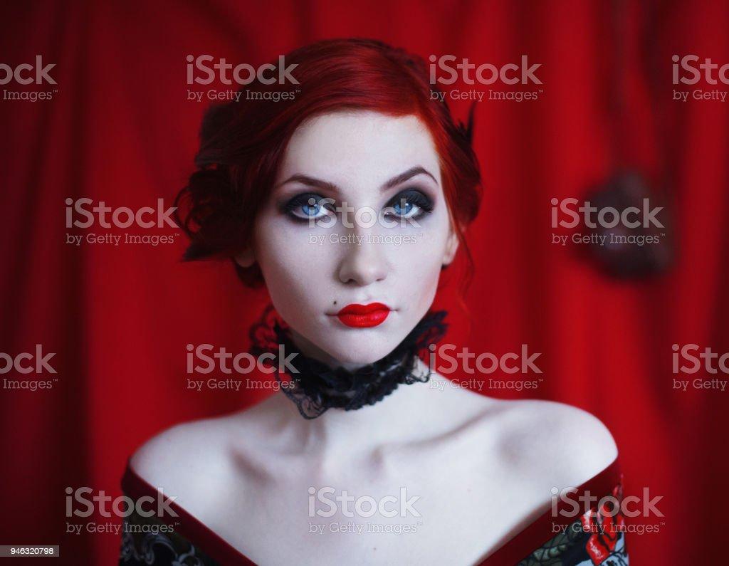 une femme avec des cheveux bouclé roux dans une robe noire et un