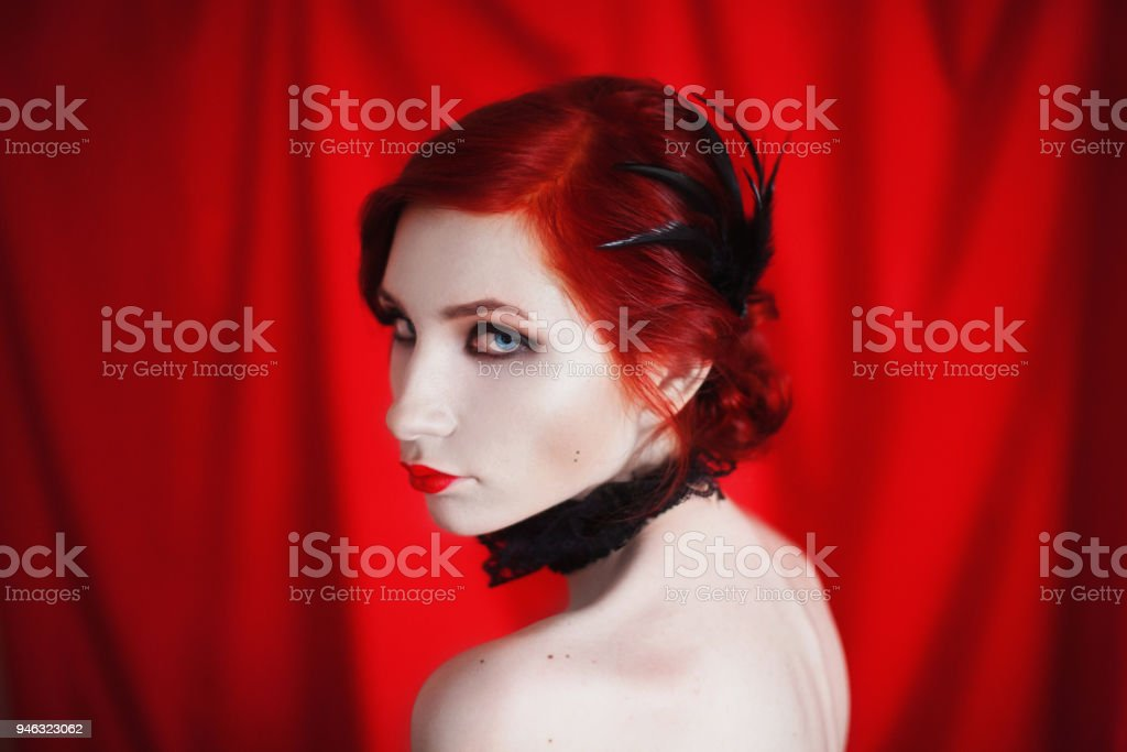 A Woman With Red Curly Hair In A Black Dress And Retro Makeup On A