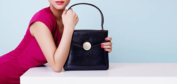 woman with red dress holding black leather purse. copy space. - leder handtaschen damen stock-fotos und bilder