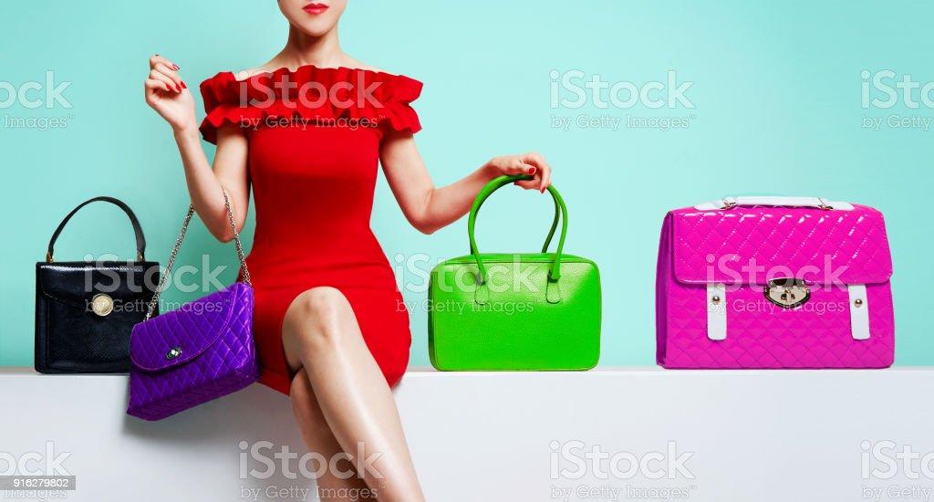 0596175765229e Vrouw met rode jurk zit met veel kleurrijke portemonnees. royalty free  stockfoto